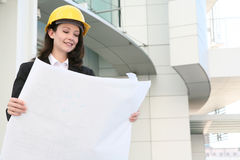 Woman Architect. A pretty woman architect inspecting the blueprints Stock Image