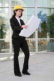 Woman Architect. A pretty woman architect inspecting the blueprints Royalty Free Stock Photos