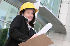 Woman Architect. A pretty woman architect holding blueprints and talking on the phone Royalty Free Stock Image