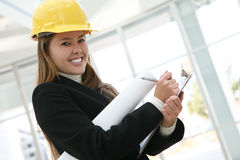 Woman Architect. A pretty woman architect holding blueprints and a clipboard Royalty Free Stock Image