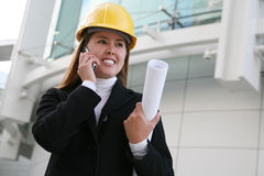 Woman Architect. A pretty woman architect holding blueprints on the phone Stock Photo
