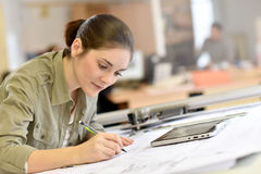 Woman architect drawing a plan at office. Woman architect working on drawing table in office Royalty Free Stock Photos