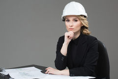 Woman architect with drawings. Beautiful girl in a building helmet Stock Image