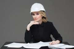 Woman architect with drawings. Beautiful girl in a building helmet Royalty Free Stock Photography