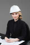 Woman architect with drawings. Beautiful girl in a building helmet Royalty Free Stock Image