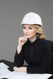 Woman architect with drawings. Beautiful girl in a building helmet Royalty Free Stock Photo