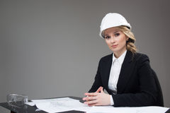 Woman architect with drawings. Beautiful girl in a building helmet Stock Photos