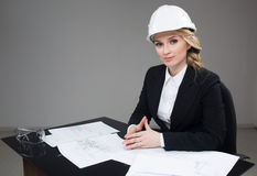 Woman architect with drawings. Beautiful girl in a building helmet Stock Photo