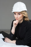Woman architect with drawings. Beautiful girl in a building helmet Royalty Free Stock Photos