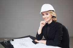 Woman architect with drawings. Beautiful girl in a building helmet Stock Photography