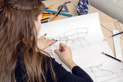 Woman architect draws a plan, design, geometric shapes by pencil on large sheet of paper at office desk. Royalty Free Stock Images