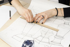 Woman architect draws a plan, design, geometric shapes by pencil on large sheet of paper at office desk. Royalty Free Stock Photo