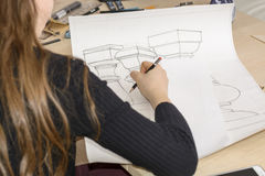 Woman architect draws a plan, design, geometric shapes by pencil on large sheet of paper at office desk. Stock Images