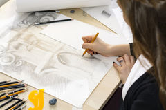 Woman architect draws a plan, design, geometric shapes by pencil on large sheet of paper at office desk. Royalty Free Stock Photography