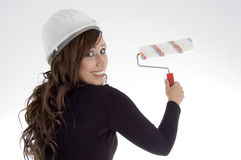 Woman with architect helmet and paint brush. Against white background Stock Photography