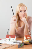 Woman architect at her work table exposing house. Young blond woman, architect at her work table exposing house Royalty Free Stock Photography