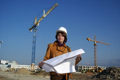 Woman architect holding blueprints against cranes Royalty Free Stock Photos