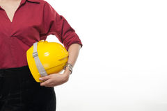 Woman architect holding safty cap. Tan skin woman architect in red shirt holding yellow safety helmet with blank copy space. Engineering and architecture Stock Photos