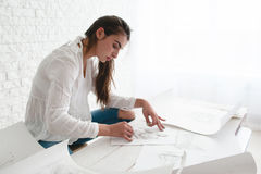 Woman architect lining sketch in studio Royalty Free Stock Photo