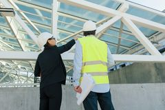 Woman architect and man builder at construction site, back view. Building, development, teamwork and people concept. Woman architect and men builder at stock photos