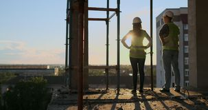 Woman architect and man builder at construction site, back view. Building, development, teamwork and people concept stock video