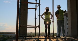 Woman architect and man builder at construction site, back view. Building, development, teamwork and people concept. Woman architect and men builder at stock video footage
