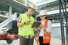 Woman architect and man builder at a construction site. Building, development, teamwork and people concept. Woman architect and men builder at a construction royalty free stock photo