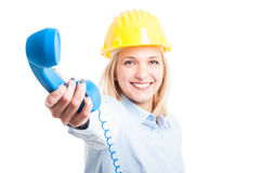 Woman architect wearing helmet showing telephone receiver Royalty Free Stock Photos