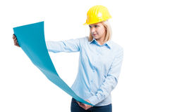 Woman architect wearing yellow helmet looking at blueprints Royalty Free Stock Image