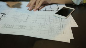 Woman architect working with blueprint sheets, layouts and drawings of the premises stock video footage