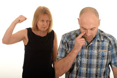 Woman arguing with a man. Angry woman with raised fist stood behind an upset man, white studio background Royalty Free Stock Images