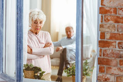 Woman after an argument. Sad older women standing in the window after an argument with her husband royalty free stock photo