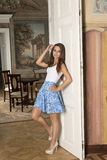Woman in aristocratic room. Indoor fashion shoot of cute brunette woman with elegant skirt, golden necklace and cute make-up posing indoor in aristocratic room Stock Image