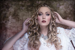 Woman with aristocratic style. Lovely blonde female with aristocratic style posing with long curly hair, stylish make-up, vintage elegant dress and precious Stock Images