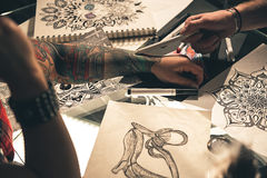 Woman arm with images locating at table. Focus on female hand with tattoo situating on desk near various art pictures. Man pointing at it. Close up Stock Photos