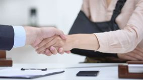 Woman with arm sling shaking lawyers hand, compensation after medical negligence