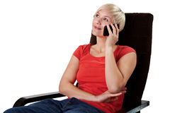 Woman in armchair calls on mobile Stock Images