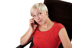 Woman in armchair calls on phone Royalty Free Stock Images