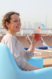 Woman in armchair on cruise liner with cocktail. Beauty woman sitting in blue armchair on cruise liner deck and holding cocktail in glass, cityscape on Stock Photos