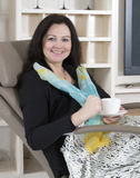 Woman in armchair with cup Royalty Free Stock Images