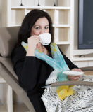 Woman in armchair with cup Stock Photos