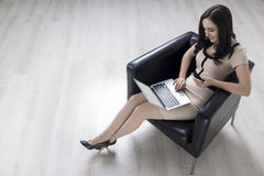 Woman in an armchair with a laptop Royalty Free Stock Photos