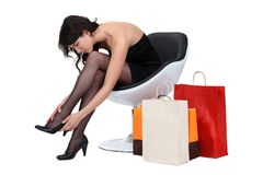 Woman in armchair with shopping Stock Photos