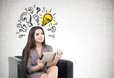 Woman in armchair, a tablet, questions, idea Stock Photography