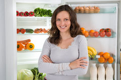 Woman With Armcrossed In Front Of Fridge. Young Happy Woman With Armcrossed In Front Of Open Fridge With Healthy Food stock photography