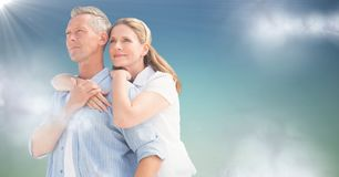 Woman with arms around man against blue green background with clouds and flare Stock Image