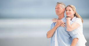 Woman with arms around man against blurry beach Royalty Free Stock Image