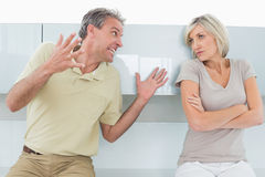 Woman with arms crossed as man argue in kitchen Royalty Free Stock Photography