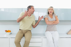 Woman with arms crossed as man argue in kitchen Royalty Free Stock Images