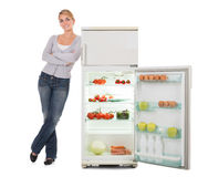 Woman With Arms Crossed Leaning On Open Refrigerator. Portrait of confident young woman leaning on open refrigerator over white background Royalty Free Stock Images